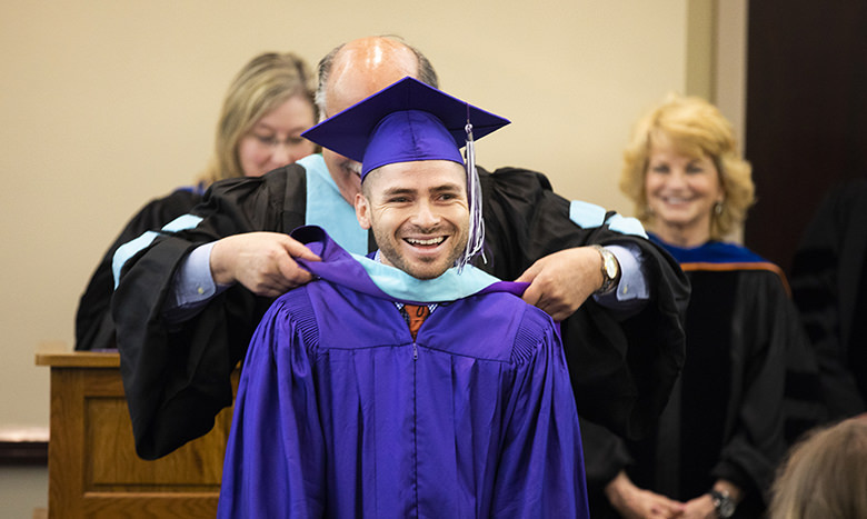 TCU student at a College of Education Master's hooding ceremony